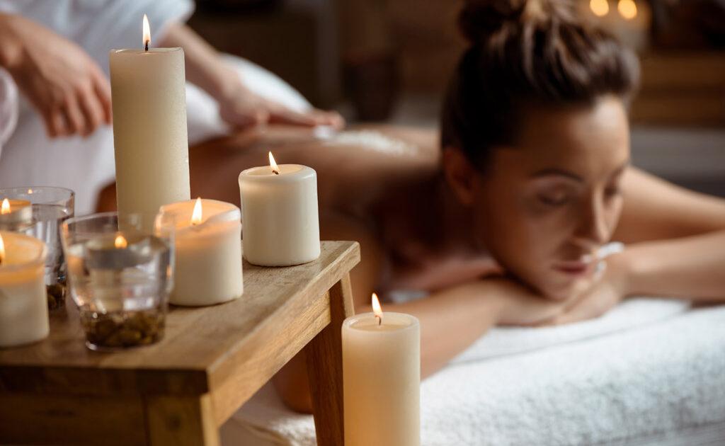 Donna che effettua un massaggio olistico e candele profumate