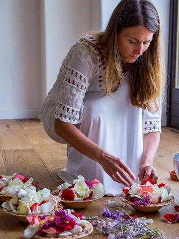 Donna che prepara fiori per rito nella sala yoga dell'Hotel Eremito - Vacanza Benessere per ritrovare te stesso