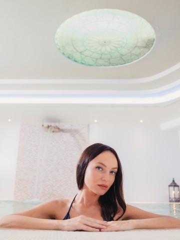 Donna nella piscina della spa di Valle di Assisi Hotel Spa & Resort - Pacchetto Benessere Esclusivo